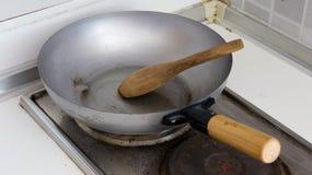 Ξύλινη κουτάλα στο τηγάνι χάλυβα έτοιμο να μαγειρεψει Στοκ Εικόνες
