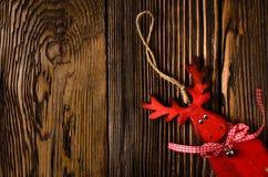 Ξύλινη κρεμώντας διακόσμηση ελαφιών στον ξύλινο πίνακα Στοκ Εικόνες