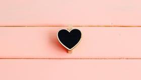 Ξύλινη μαύρη καρδιά στο ρόδινο ξύλινο πίνακα Τοπ όψη βαλεντίνος Στοκ φωτογραφίες με δικαίωμα ελεύθερης χρήσης