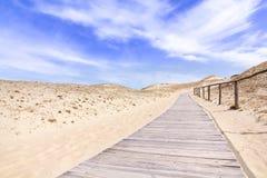 Ξύλινη πάροδος στους αμμόλοφους άμμου με το μπλε ουρανό και τα σύννεφα Στοκ Φωτογραφία