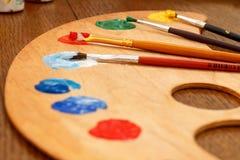 Ξύλινη παλέτα με την τοποθέτηση στα χρώματα και τα πινέλα Στοκ φωτογραφία με δικαίωμα ελεύθερης χρήσης