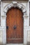 Ξύλινη πόρτα με το χαρασμένο διακοσμημένο πέτρα πλαίσιο Στοκ Εικόνες