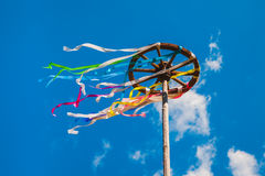 Ξύλινη ρόδα με τις ζωηρόχρωμες κορδέλλες στο υπόβαθρο μπλε ουρανού Στοκ φωτογραφία με δικαίωμα ελεύθερης χρήσης