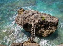 Ξύλινη σκάλα που συνδέεται με το βράχο στη θάλασσα Στοκ Φωτογραφίες