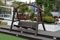 Ξύλινη ταλάντευση πάγκων στον κήπο με τα λουλούδια Στοκ Εικόνες