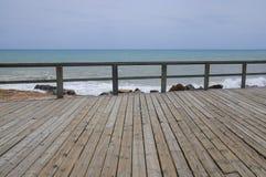Ξύλινοι θαλάσσιος περίπατος και κιγκλίδωμα από την κυανή μπλε Μεσόγειο και το γ Στοκ Εικόνα