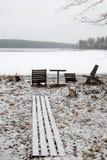 Ξύλινοι καρέκλες και πίνακας στην παγωμένη λίμνη Στοκ Φωτογραφίες