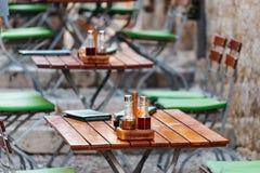Ξύλινοι καρέκλες και πίνακες με επιλογές, ένα άλας και ένα έλαιο σε έναν ευρωπαϊκό καφέ ή ένα εστιατόριο οδών Στοκ φωτογραφίες με δικαίωμα ελεύθερης χρήσης