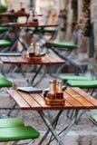 Ξύλινοι καρέκλες και πίνακες με επιλογές, ένα άλας και ένα έλαιο σε έναν ευρωπαϊκό καφέ ή ένα εστιατόριο οδών Στοκ Εικόνα