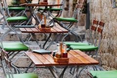 Ξύλινοι καρέκλες και πίνακες με επιλογές, ένα άλας και ένα έλαιο σε έναν ευρωπαϊκό καφέ ή ένα εστιατόριο οδών Στοκ Εικόνες