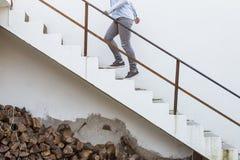 Ξύλινοι κορμοί που συσσωρεύονται κάτω από τα σκαλοπάτια ενώ μια νέα γυναίκα πηγαίνει upstai Στοκ Εικόνα