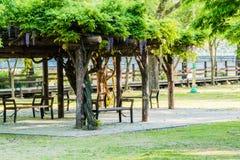 Ξύλινοι πάγκοι πάρκων κάτω από μια κάλυψη των φτερών Στοκ φωτογραφία με δικαίωμα ελεύθερης χρήσης