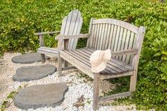 Ξύλινοι πάγκος και καρέκλα με ένα καπέλο που αφήνεται στο βραχίονα Στοκ Φωτογραφία