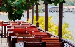 Ξύλινοι πίνακες και έδρες σε ένα ανοικτό εστιατόριο πεζουλιών Στοκ φωτογραφίες με δικαίωμα ελεύθερης χρήσης