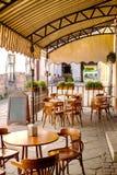 Ξύλινοι πίνακες και καρέκλες κάτω από έναν θόλο κοντά στον παλαιό καφέ Στοκ Φωτογραφία