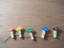 Ξύλινοι συνδετήρες στην καφετιά σειρά ως ζωηρόχρωμη εργάσιμη ημέρα Στοκ Φωτογραφία
