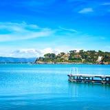 Ξύλινος αποβάθρα ή λιμενοβραχίονας σε μια μπλε θάλασσα. Παραλία σε Argentario, Τοσκάνη, Ιταλία Στοκ εικόνα με δικαίωμα ελεύθερης χρήσης