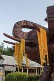 Ξύλινος επικεφαλής ελέφαντας χάραξης και κίτρινη πλαστική γιρλάντα λουλουδιών, θόριο Στοκ Φωτογραφία