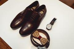 Ξύλινος δεσμός τόξων, καφετιά παπούτσια δέρματος, ζώνη, ρολόι Γαμήλιο πρωί νεόνυμφων Κλείστε επάνω των σύγχρονων εξαρτημάτων ατόμ Στοκ Εικόνες
