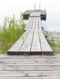 Ξύλινος θαλάσσιος περίπατος που οδηγεί έξω στο σύνολο ή το επιπλέον σώμα Στοκ Εικόνα