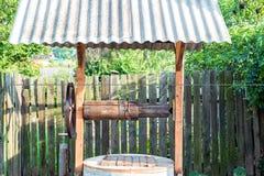 Ξύλινος καλά κοντά στο φράκτη με τις αγγελίες Στοκ Φωτογραφία