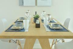 Ξύλινος να δειπνήσει πίνακας με να δειπνήσει το σύνολο στο σύγχρονο ύφος Στοκ Εικόνες