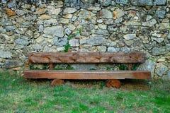 Ξύλινος πάγκος μπροστά από έναν τοίχο βράχου στοκ εικόνες