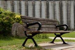 Ξύλινος πάγκος σε έναν πράσινο χορτοτάπητα Στοκ φωτογραφία με δικαίωμα ελεύθερης χρήσης