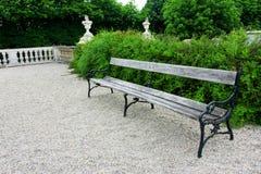 Ξύλινος πάγκος σε ένα πράσινο πάρκο με ποικίλους θάμνους Στοκ εικόνες με δικαίωμα ελεύθερης χρήσης