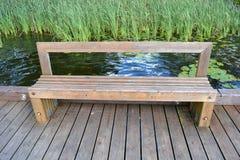 Ξύλινος πάγκος στην ακτή λιμνών στο πάρκο Στοκ φωτογραφία με δικαίωμα ελεύθερης χρήσης