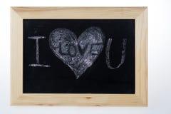 Ξύλινος πίνακας για τις σημειώσεις σε μια μορφή καρδιών με την άσπρη κιμωλία λέξεων σ' αγαπώ Στοκ φωτογραφία με δικαίωμα ελεύθερης χρήσης