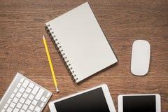 Ξύλινος πίνακας γραφείων με το σημειωματάριο, κίτρινο μολύβι, ταμπλέτα, keyboa Στοκ εικόνα με δικαίωμα ελεύθερης χρήσης
