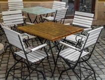 Ξύλινος πίνακας και άσπρες και μαύρες καρέκλες στον καφέ Στοκ φωτογραφία με δικαίωμα ελεύθερης χρήσης