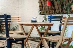 Ξύλινος πίνακας και μαύρες καρέκλες στον κήπο καφέδων Στοκ Εικόνα