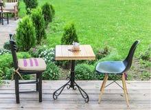Ξύλινος πίνακας και μαύρες καρέκλες στον κήπο καφέδων Στοκ εικόνες με δικαίωμα ελεύθερης χρήσης