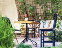 Ξύλινος πίνακας και μαύρη καρέκλα στον κήπο καφέδων Στοκ φωτογραφία με δικαίωμα ελεύθερης χρήσης