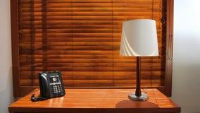 Ξύλινος πίνακας με το λαμπτήρα και τηλέφωνο με τα ξύλινα παραθυρόφυλλα στο υπόβαθρο Στοκ Φωτογραφίες