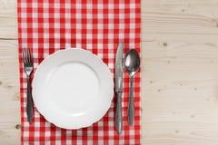 Ξύλινος πίνακας με το ελεγμένο κόκκινο πιάτο, το μαχαίρι, το κουτάλι και το δίκρανο τραπεζομάντιλων Στοκ Εικόνα