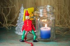 Ξύλινος στρατιώτης παιχνιδιών στην κόκκινα ομοιόμορφα διακόσμηση και το κερί Στοκ Φωτογραφία