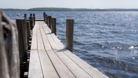 Ξύλινος τίτλος αποβαθρών στο νερό σε βάθος Στοκ εικόνα με δικαίωμα ελεύθερης χρήσης