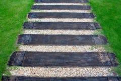 Ξύλινος τρόπος σκαλοπατιών στον πράσινο κήπο Στοκ Εικόνα