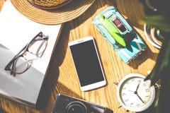 Ξύλινο δάπεδο με το φως του ήλιου, εγκαταστάσεις, ξυπνητήρια, παιχνίδια αυτοκινήτων, κινητό τηλέφωνο, κάμερες, καπέλα Στοκ Φωτογραφία