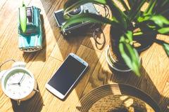 Ξύλινο δάπεδο με το φως του ήλιου, εγκαταστάσεις, ξυπνητήρια, παιχνίδια αυτοκινήτων, κινητό τηλέφωνο, κάμερες, καπέλα Στοκ Εικόνες