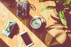 Ξύλινο δάπεδο με το φως του ήλιου, εγκαταστάσεις, ξυπνητήρια, παιχνίδια αυτοκινήτων, κινητό τηλέφωνο, κάμερες, καπέλα Στοκ φωτογραφία με δικαίωμα ελεύθερης χρήσης