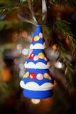 Ξύλινο λαμπρά χρωματισμένο χριστουγεννιάτικο δέντρο παιχνιδιών Χριστουγέννων που κρεμά επάνω στοκ εικόνα με δικαίωμα ελεύθερης χρήσης