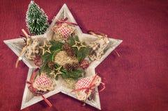 Ξύλινο αστέρι στο κόκκινο υπόβαθρο που διακοσμείται με το στεφάνι Χριστουγέννων Στοκ Εικόνες