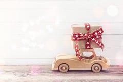 Ξύλινο αυτοκίνητο παιχνιδιών με ένα κιβώτιο δώρων στη στέγη Άσπρο ξύλινο backgro Στοκ εικόνες με δικαίωμα ελεύθερης χρήσης