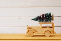 Ξύλινο αυτοκίνητο που φέρνει ένα χριστουγεννιάτικο δέντρο Στοκ Εικόνα