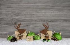 Ξύλινο γκρίζο υπόβαθρο Χριστουγέννων με τον τάρανδο, τις σφαίρες και τα δώρα Στοκ Φωτογραφίες