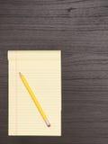 Ξύλινο γραφείο, κίτρινο σημειωματάριο, μολύβι Στοκ Φωτογραφία
